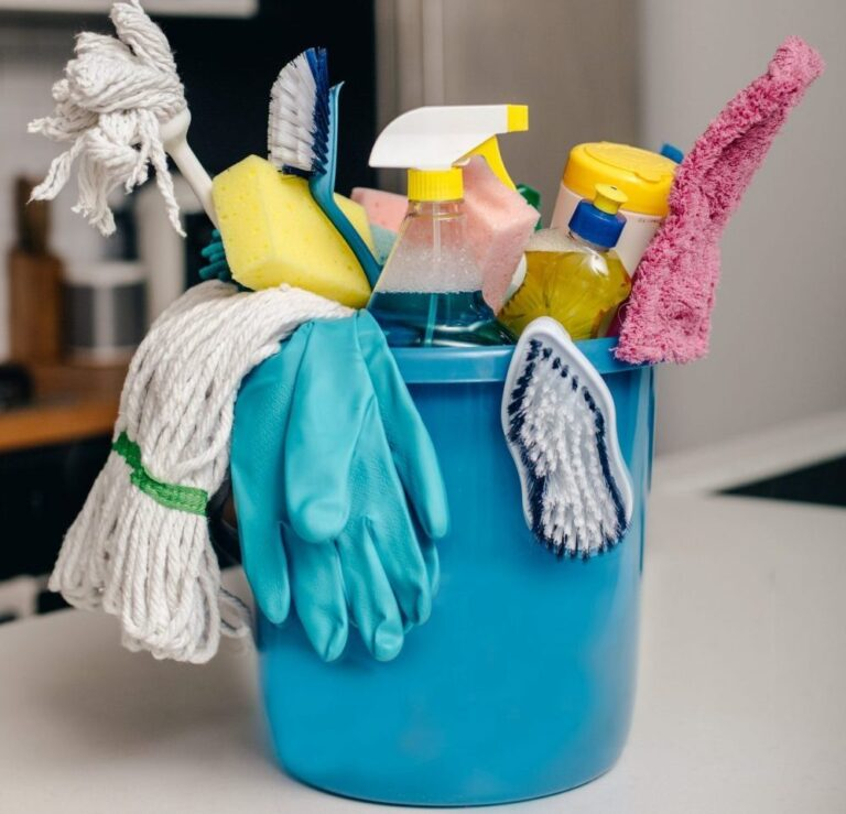 Cleaning products, detergents and chemicals in blue plastic bucket on kitchen worktop.