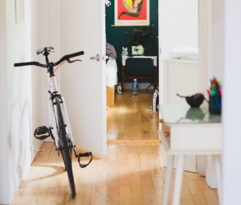 Clean, bright, light and airy hallway with wooden floors bicycle propped up against wall door to bedroom open.