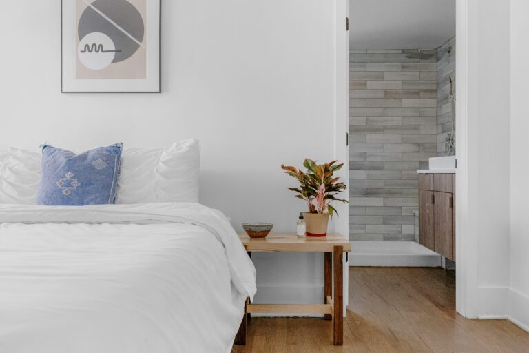 Bedroom with double bed white walls, white bed linen, wooden bedside table with plant, wooden floor and en suite.
