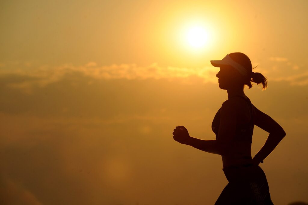 Lady running wearing cap in silhouette, sunset background.