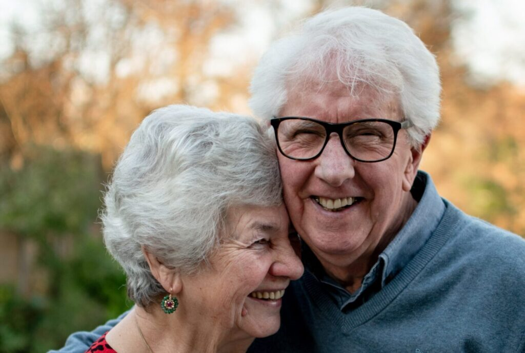 Retired older couple hugging and looking happy and smiling on a sunny day