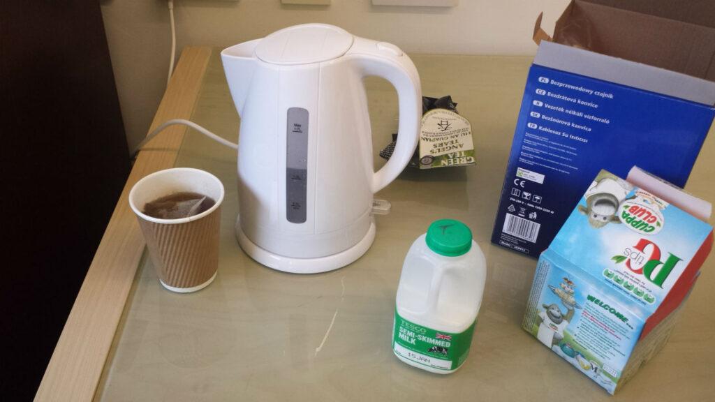 Office kettle, box of tea bags, bottle of semi-skimmed milk, tea in disposable cup on sideboard in office kitchen