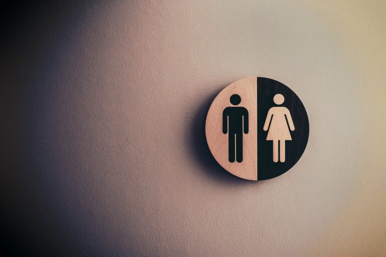 Office toilets - male / female circular sign on wall illustrated by man symbol and woman symbol