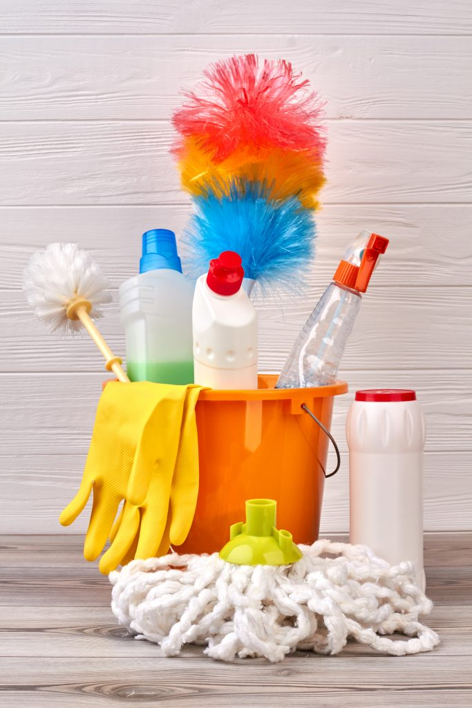 cleaning supplies including duster, mop head and rubber gloves in bucket