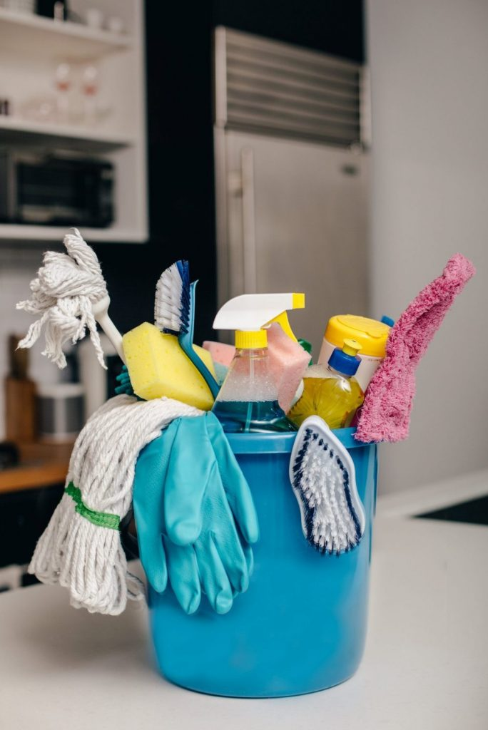 cleaning supply bucket containing glass cleaner, mop head etc.